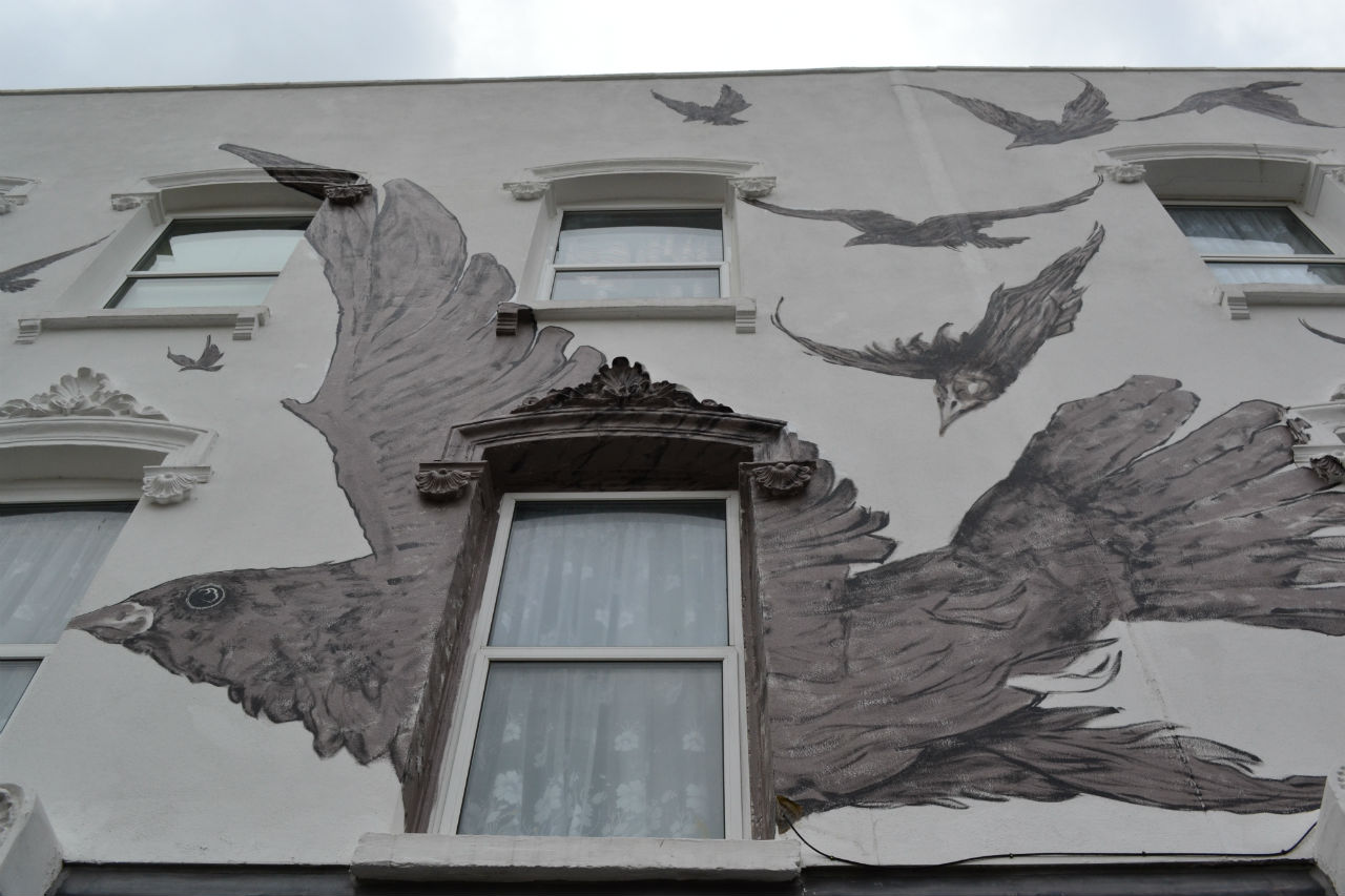 Exterior of the Birds pub - a wall of bird paintings