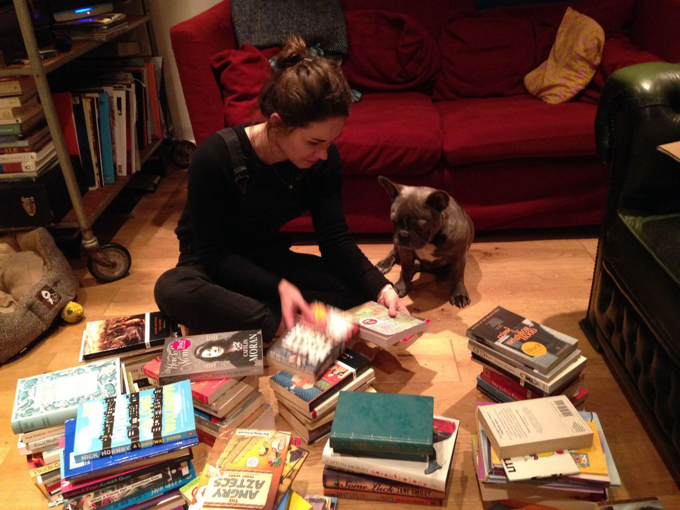 Aimée sitting with her dog looking through books to sell in Phlox Books