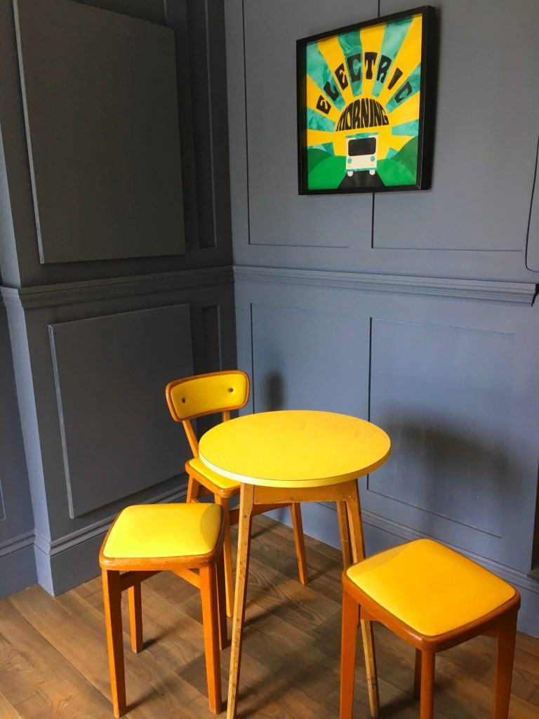 Dark blue walls, yellow coffee table and chairs in Curved Brick Co